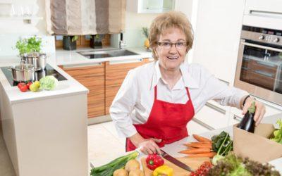 Seniorin freut sich aufs kochen mit frischem Gemüse